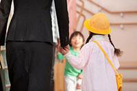 保育所の玄関に立つ母親と子供
