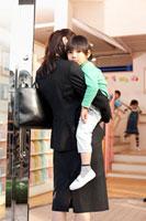 保育所の玄関で子供を抱く母親