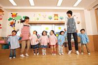 教室で遊ぶ幼稚園児と幼稚園教諭