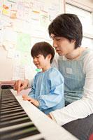 ピアノを弾く男の子と幼稚園教諭