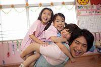 子供3人を背負う幼稚園教諭 11014028328| 写真素材・ストックフォト・画像・イラスト素材|アマナイメージズ