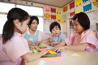 折り紙をする子供3人と幼稚園教諭 11014028329| 写真素材・ストックフォト・画像・イラスト素材|アマナイメージズ