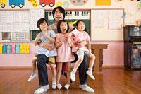 子供3人を抱く幼稚園教諭 11014028336| 写真素材・ストックフォト・画像・イラスト素材|アマナイメージズ