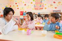 弁当を食べる幼稚園児と幼稚園教諭