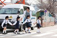 バスの前を並んで歩く幼稚園児と幼稚園教諭 11014028354| 写真素材・ストックフォト・画像・イラスト素材|アマナイメージズ