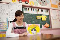 紙芝居を見せる幼稚園教諭 11014028365| 写真素材・ストックフォト・画像・イラスト素材|アマナイメージズ