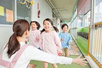 幼稚園教諭の元に駆け寄る幼稚園児 11014028376| 写真素材・ストックフォト・画像・イラスト素材|アマナイメージズ