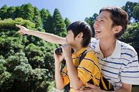 屋外で遠くを見つめる父親と息子