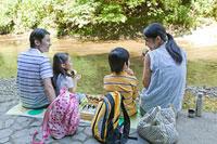 川辺で弁当を食べる家族4人