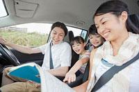 車の中で地図を見る家族4人