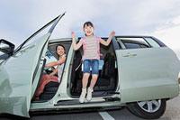 車から降りる女の子とドアを開ける母親