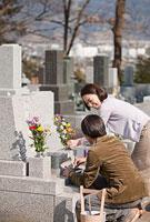 カジュアルウェアでお墓に花を供える夫婦