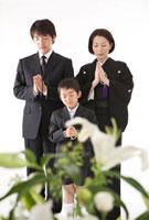 喪服姿で手を合わせる家族と花束