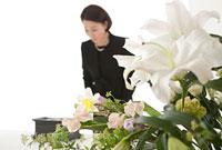 花束と焼香台の前でお辞儀をする喪服姿の女性  斜め