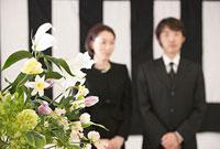 鯨幕の前に立つ喪服姿の夫婦と花束