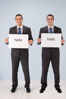 Businessmen holding hello signs
