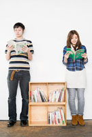 Young man and woman reading books