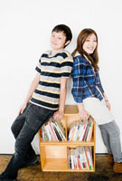 Young man and woman leaning on bookshelf