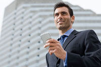 A businessman smiling whilst holding a mobile phone