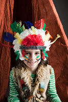 Young boy dressed up in Native American outfit,with teepee