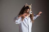 Young girl wearing tiger mask,roaring