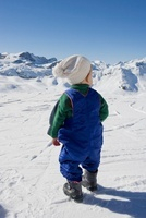 Young boy standing looking at mountains in snow