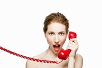 Angry woman holding red telephone