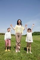 Mother with two children in field with arms up