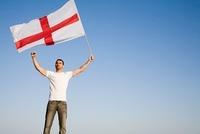 Man holding St George's Cross flag in the air 11015204499  写真素材・ストックフォト・画像・イラスト素材 アマナイメージズ