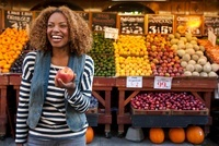 Young woman holding peach from market stall, smiling
