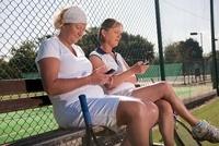 Senior women texting on tennis court
