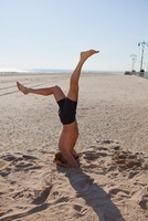Man performing headstand on a beach