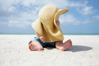 Baby boy playing with mother's sun hat on the beach