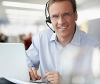 Businessman using laptop and wearing headset, portrait