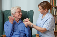 Carer assisting senior man with hand weights