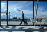 Businessman walking with suitcase outside airport