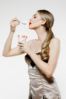 Young woman eating strawberries and cream