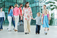 Mother and children walking through airport