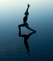 Woman in yoga pose in lake