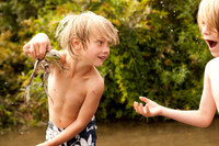 Boy holding frog up whilst friend looks on in amazement 11015209360| 写真素材・ストックフォト・画像・イラスト素材|アマナイメージズ