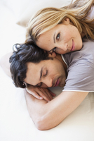 Young couple snuggling in bed