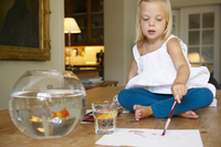 Girl on table,painting next to goldfish