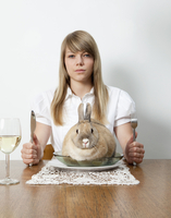 Woman with living rabbit on her plate