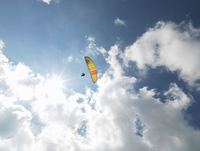 Senior paraglider in midair against sky