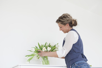Woman putting tulips into a vase