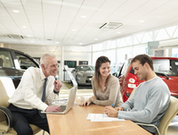 Salesman and customers in car dealership