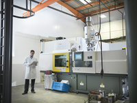 Scientist with plastic moulding machine