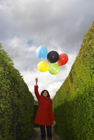 Lady holding balloons in a maze