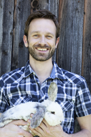 Man holding rabbit outdoors
