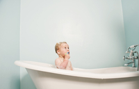 Toddler sitting in bubble bath